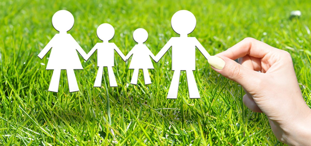 cut out paper figures of family against a grass background